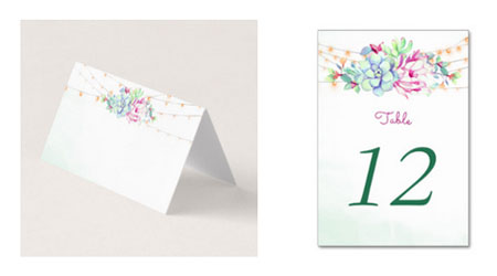 Wedding place cards and table number cards featuring a watecolor desert design with cactus, succulents and string lights.