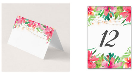 Wedding reception place card and table number card featuring a tropical sting light watercolor design with hibiscus, frangipani and tropical foliage.