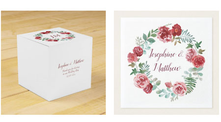 Square wedding favor box and wedding napkins featuring a watercolor burgundy rose and foliage wreath. The favor box has a monogram inside the wreath with a thank you message on the side.