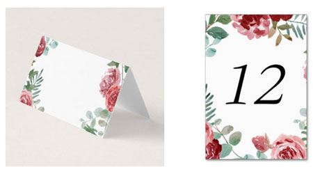 Wedding reception place cards and table number cards with a burgundy red rose and green foliage watercolor design.